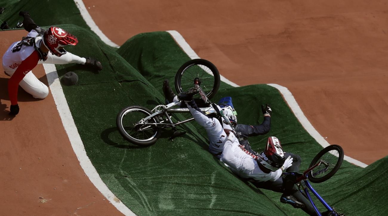 David Graf of Switzerland, left, and Maris Strombergs of Latvia, right, fall during the BMX cycling quarterfinals during the 2016 Summer Olympics in Rio de Janeiro, Brazil, Thursday, Aug. 18, 2016. (AP Photo/Pavel Golovkin)