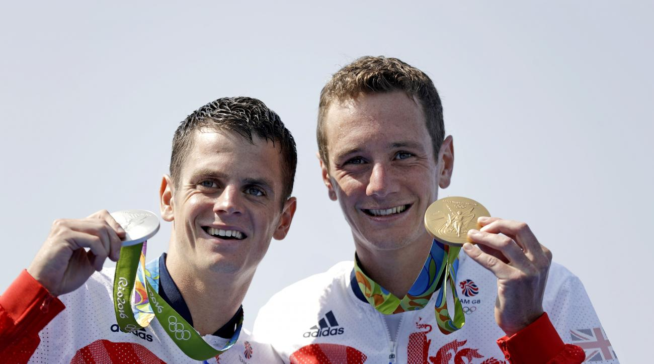 Gold medalist Britain's Alistair Brownlee, right, stands with his brother, silver medalist Jonathan Brownlee, after they finished first and second in the men's triathlon event at the 2016 Summer Olympics in Rio de Janeiro, Brazil, Thursday, Aug. 18, 2016.
