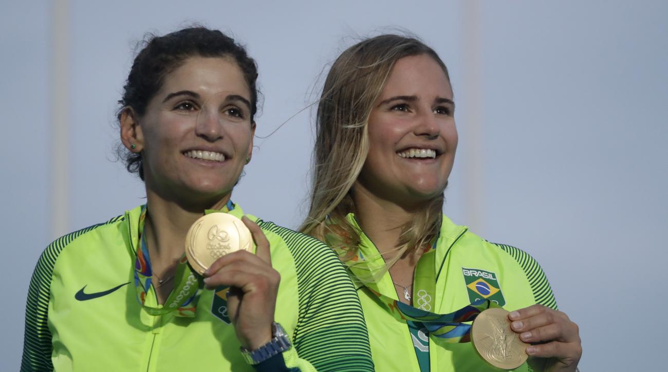 Brazil's Kahena Kunze, right, and Martine Grael celebrate their gold medal at the end of the 49er FX women race during the 2016 Summer Olympics in Rio de Janeiro, Brazil, Thursday, Aug. 18, 2016. (AP Photo/Gregorio Borgia)