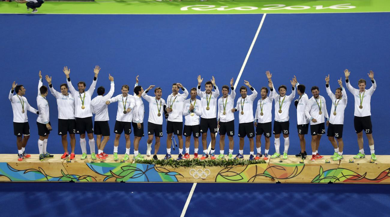 Players from Argentina stand on the podium wave to their fans after they received their gold medal winners of the men's field hockey competition at the 2016 Summer Olympics in Rio de Janeiro, Brazil, Thursday, Aug. 18, 2016. (AP Photo/Hussein Malla)