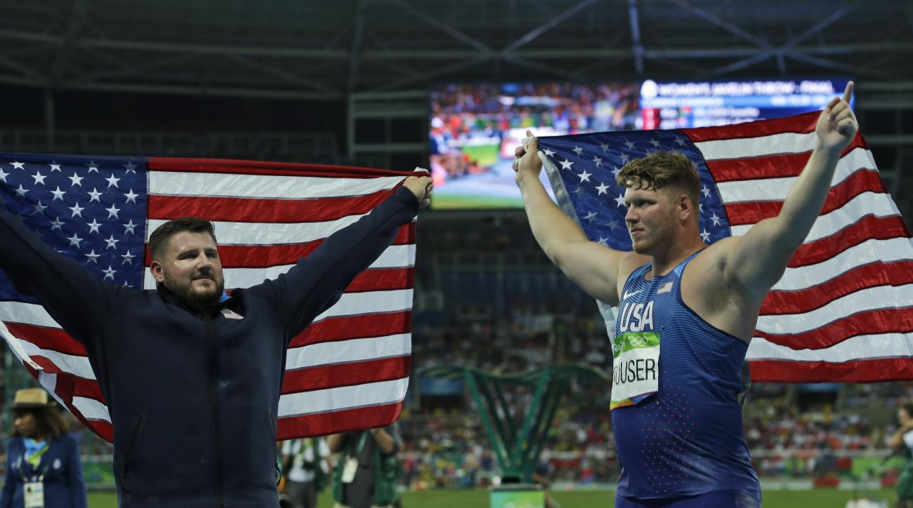 Gold medallist for the men's shot put United States' Ryan Crouser, right, and compatriot and silver medalist Joe Kovacs celebrate with their national flag during the athletics competitions of the 2016 Summer Olympics at the Olympic stadium in Rio de Janei