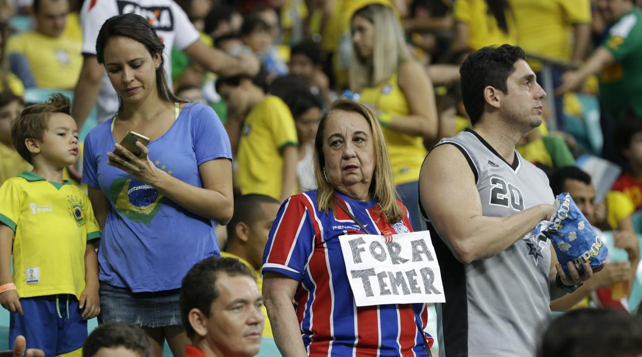 FILE - In this Aug. 10, 2016 file photo, a woman wears a sign protesting Brazil's acting President Michel Temer   before a men' s Olympic football match between Brazil and Denmark in Salvador, Brazil. Top Brazilian politicians have stayed away from the ve