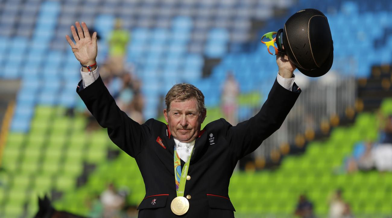 Gold medalist Nick Skelton, of Britain, acknowledges the crowd during a medal ceremony for the equestrian individual jumping competition at the 2016 Summer Olympics in Rio de Janeiro, Brazil, Friday, Aug. 19, 2016. (AP Photo/Jae C. Hong)