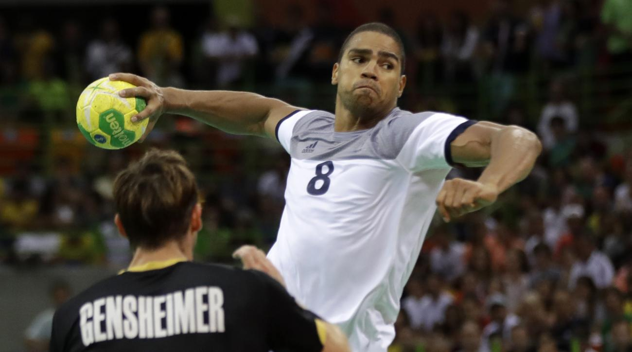 France's Daniel Narcisse scores a goal past Germany's Uwe Gensheimer, left, during the men's semifinal handball match between France and Germany at the 2016 Summer Olympics in Rio de Janeiro, Brazil, Friday, Aug. 19, 2016. (AP Photo/Ben Curtis)
