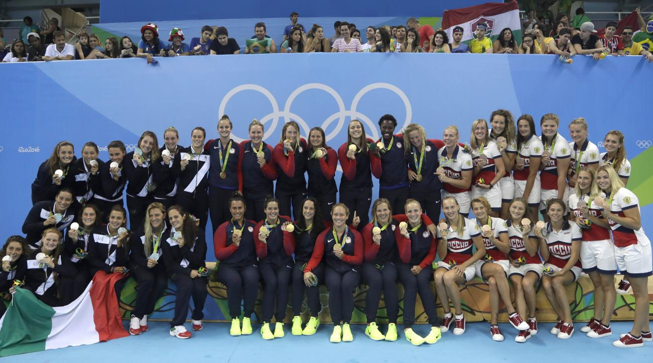 Members of Italy, United States and Russia women water polo teams, from left to right, pose for media during the medals ceremony at the 2016 Summer Olympics in Rio de Janeiro, Brazil, Friday, Aug. 19, 2016. (AP Photo/Sergei Grits)