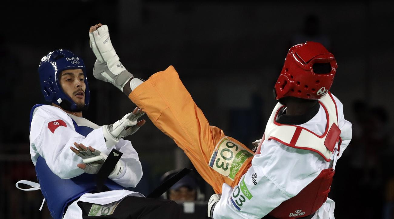 Oussama Oelslati of Tunisia, left, and Cheick Sallah Junior Cisse of Ivory Coast compete in a men's Taekwondo 80-kg quarterfinal at the 2016 Summer Olympics in Rio de Janeiro, Brazil, Friday, Aug. 19, 2016. (AP Photo/Andrew Medichini)