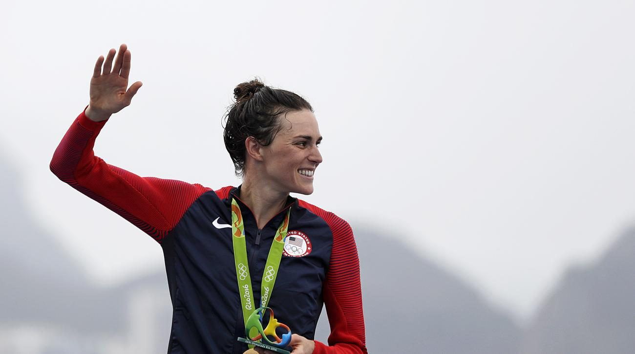 Gwen Jorgensen, of the United States, waves after receiving the gold medal for winning the women's triathlon event on Copacabana beach at the 2016 Summer Olympics in Rio de Janeiro, Brazil, Saturday, Aug. 20, 2016. (AP Photo/David Goldman)