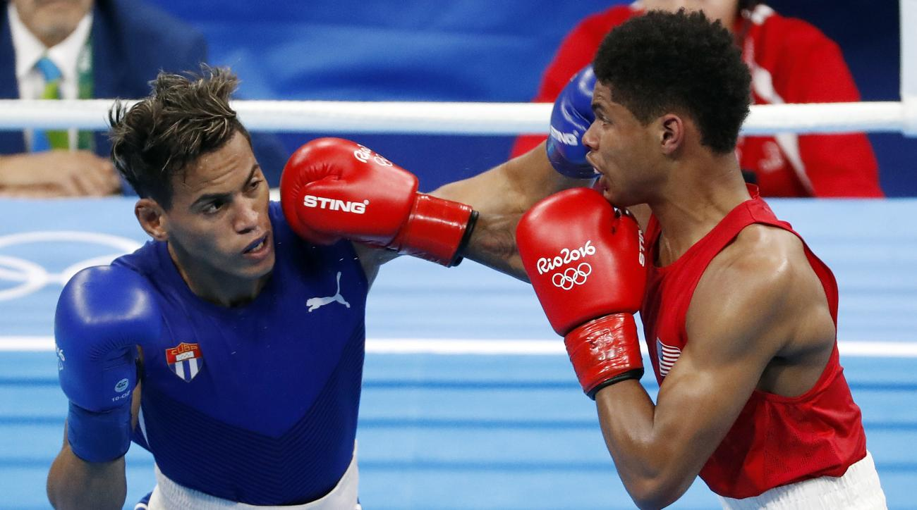 Cuba's Robeisy Ramirez, left, and United States' Shakur Stevenson exchange punches during a men's bantamweight 56-kg final boxing match at the 2016 Summer Olympics in Rio de Janeiro, Brazil, Saturday, Aug. 20, 2016. (AP Photo/Vincent Thian)