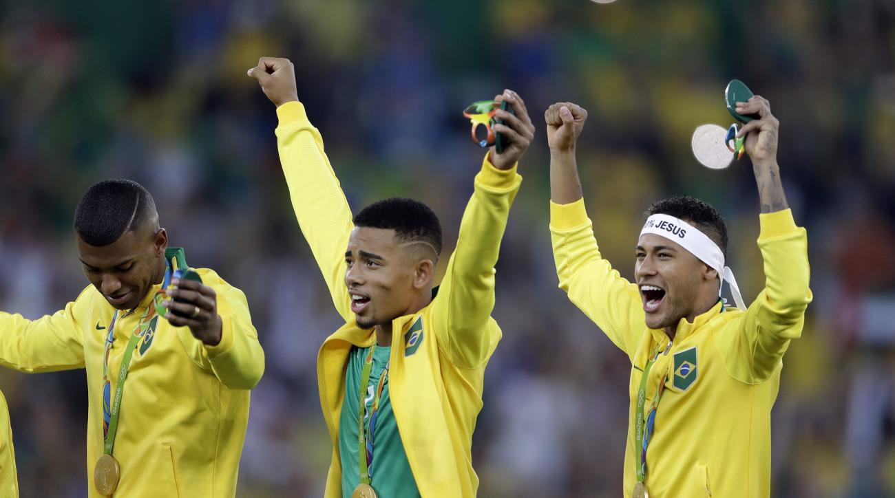 Brazil's Neymar, right, and Gabriel Jesus, center, celebrate after receiving their gold medals after the final match of the men's Olympic football tournament between Brazil and Germany at the Maracana stadium in Rio de Janeiro, Brazil, Saturday Aug. 20, 2