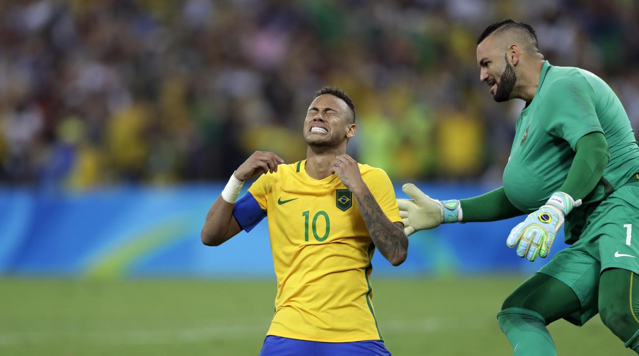 Brazil's Neymar cries as he kneels down to celebrate with teammate goalkeeper Weverton after scoring the decisive penalty kick during the final match of the men's Olympic football tournament between Brazil and Germany at the Maracana stadium in Rio de Jan