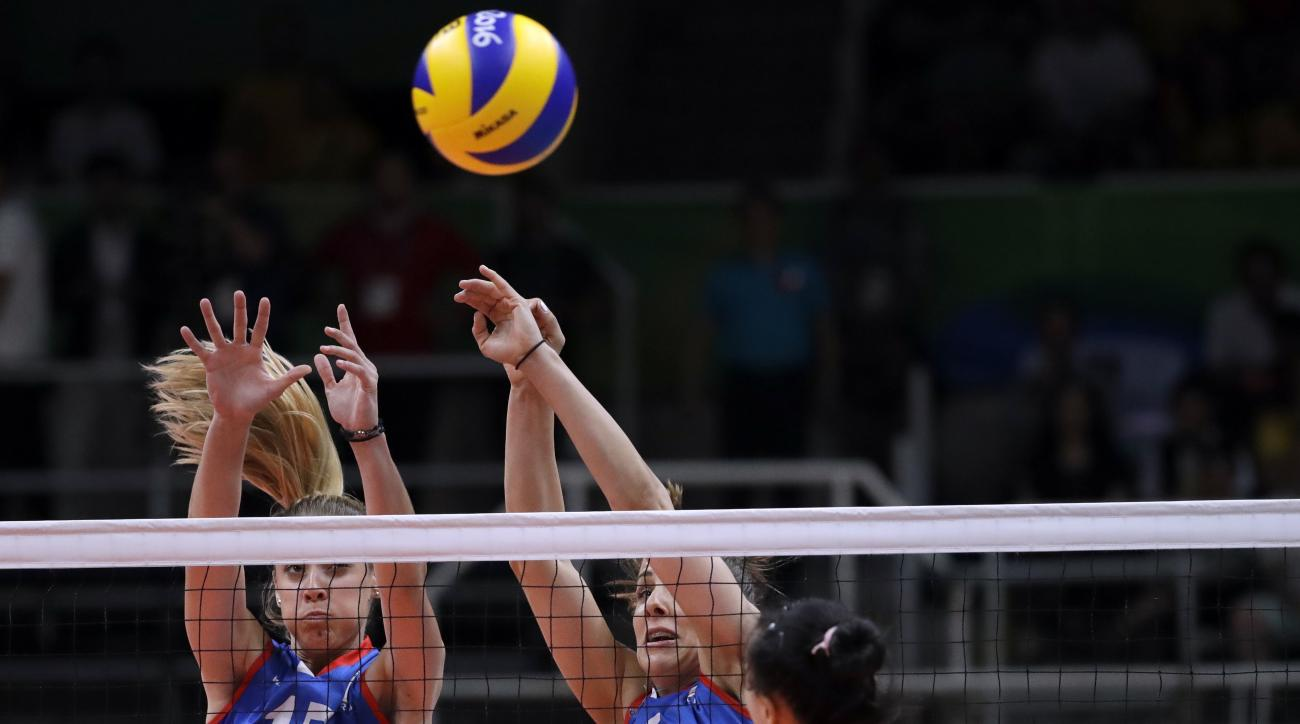 China's Zhang Changning, right, spikes as Serbia's Jovana Stevanovic, left, and Tijana Malesevic defend during a women's gold medal volleyball match at the 2016 Summer Olympics in Rio de Janeiro, Brazil, Saturday, Aug. 20, 2016. (AP Photo/Jeff Roberson)