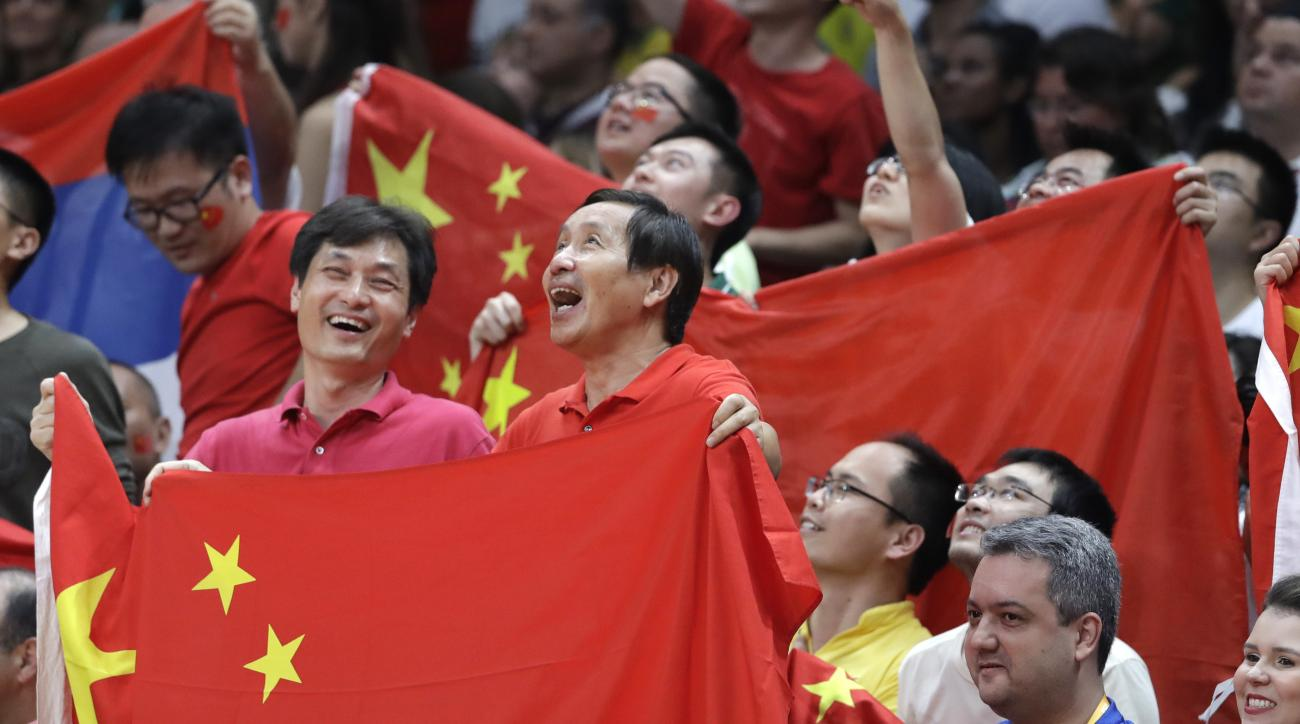 Fans hold the flag of China during a women's gold medal volleyball match between China and Serbia at the 2016 Summer Olympics in Rio de Janeiro, Brazil, Saturday, Aug. 20, 2016. (AP Photo/Jeff Roberson)