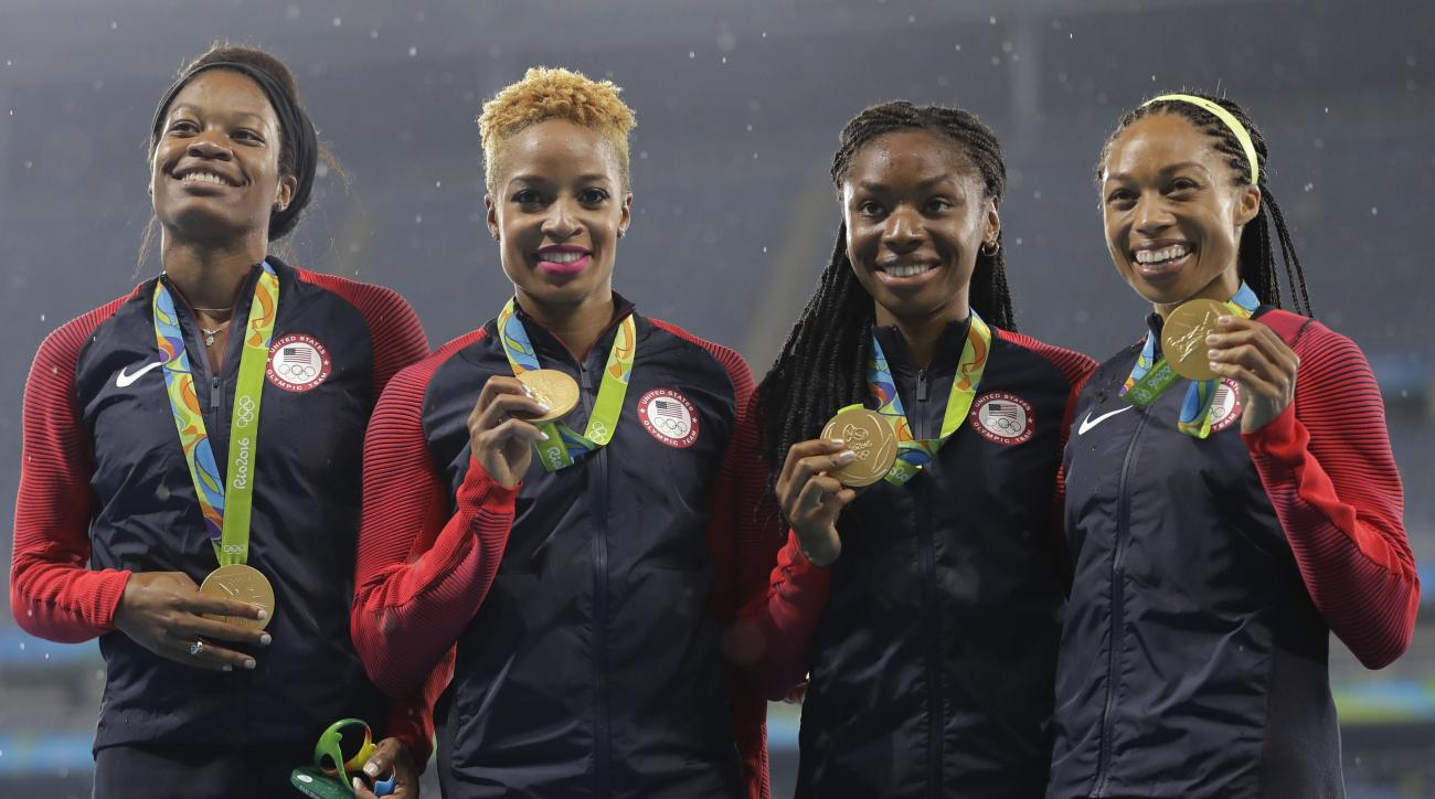 The United States women's 4x400 meter relay team members, Courtney Okolo, Natasha Hastings, Phyllis Francis and Allyson Felix celebrate their gold medals on the podium during athletics competitions at the Summer Olympics inside Olympic stadium in Rio de J