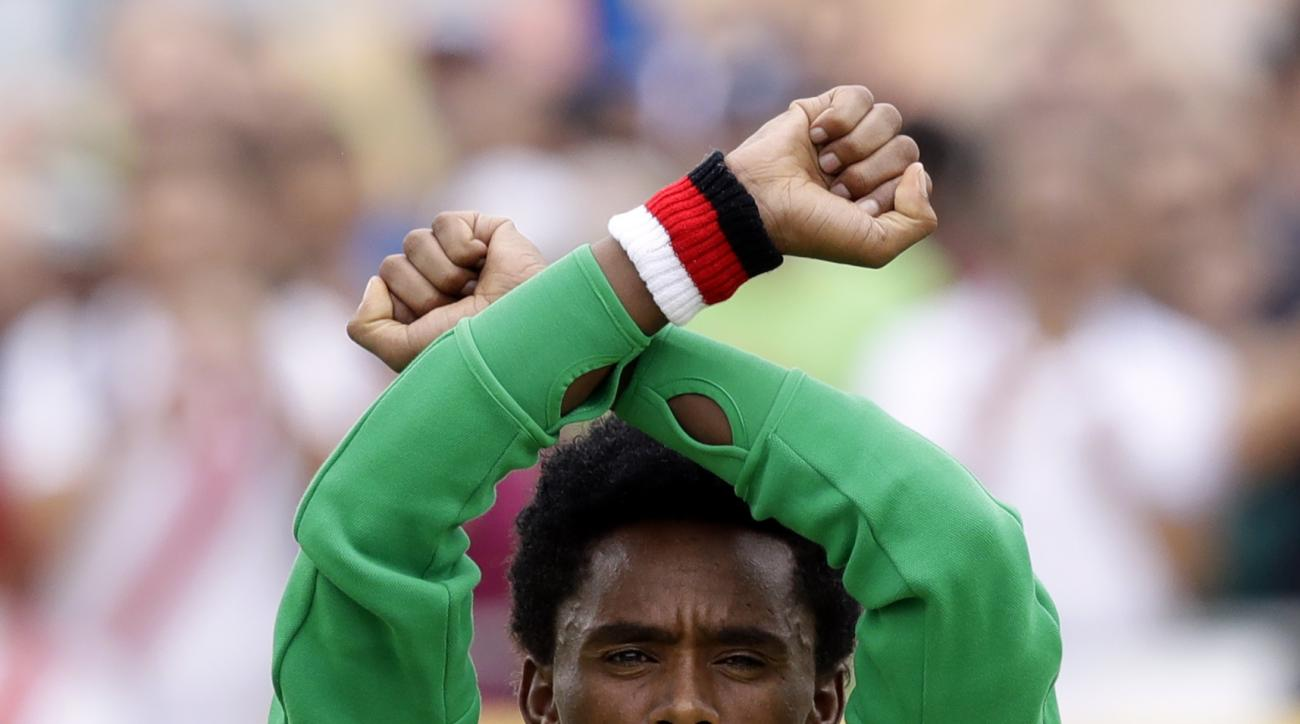 Silver medalist Feyisa Lilesa, of Ethiopia, acknowledges applause during an award ceremony after the men's marathon at the 2016 Summer Olympics in Rio de Janeiro, Brazil, Sunday, Aug. 21, 2016. (AP Photo/Robert F. Bukaty)