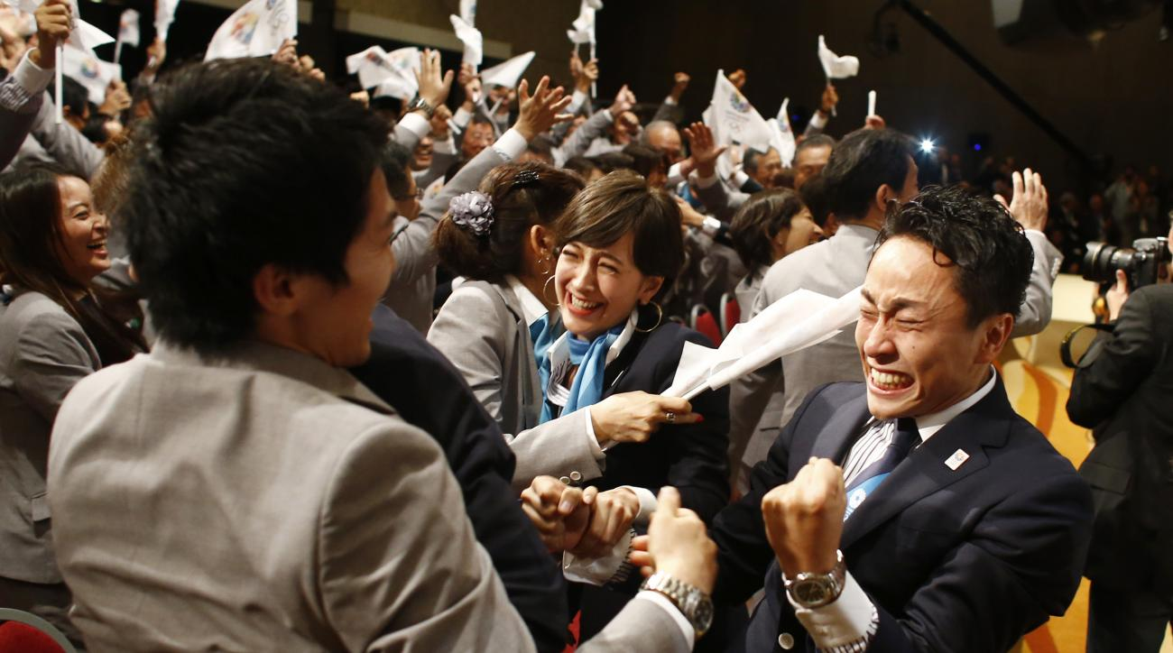FILE - In this Sept. 7, 2013 file photo, members of the Tokyo 2020 delegation celebrate after Tokyo was awarded the 2020 Olympic Games during the 125th IOC session in Buenos Aires, Argentina. The next three Olympics are headed for relatively calmer ports