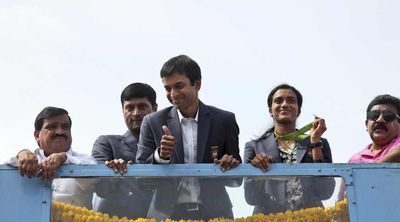Pusarla Sindhu, second from right, one of the only two Indians to win medals at the just concluded Rio Olympics, displays her silver medal as she is brought home in a procession along with her coach Pullela Gopichand, third from left, upon their arrival a