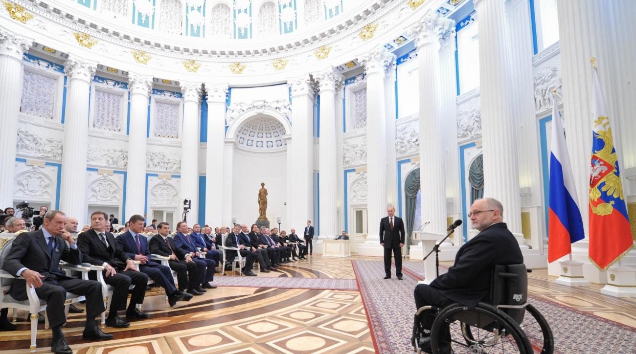 FILE - In this file photo taken on Monday, March 24, 2014, Sir Philip Craven, President of the International Paralympic Committee, right, speaks as Russian President Vladimir Putin, standing background center, listens to him during an awards ceremony in t