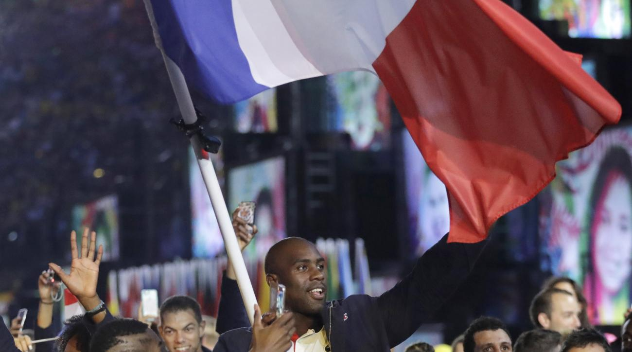 FILE  - This Friday, Aug. 5, 2016 file photo shows Teddy Riner carrying the flag of France during the opening ceremony for the 2016 Summer Olympics in Rio de Janeiro, Brazil. Frances president hosts the French athletes back from the Olympics of Rio de Jan