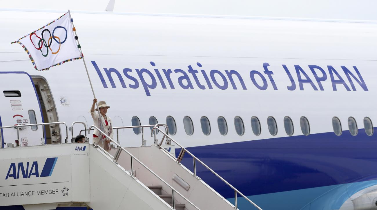 Tokyo Gov. Yuriko Koike waves the Olympic flag upon arrival at Haneda international airport in Tokyo, Wednesday, Aug. 24, 2016. The Olympic flag arrived in Tokyo, host of the next 2020 Summer Games. (AP Photo/Eugene Hoshiko)