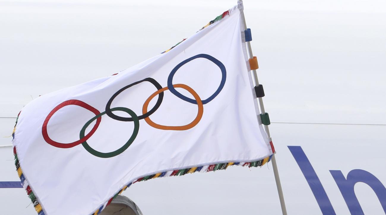 Tokyo Gov. Yuriko Koike waves the Olympic flag upon arrival at Haneda international airport in Tokyo, Wednesday, Aug. 24, 2016. The Olympic flag arrived in Tokyo, host of the next 2020 Summer Games. (AP Photo/Eugene Hoshiko)