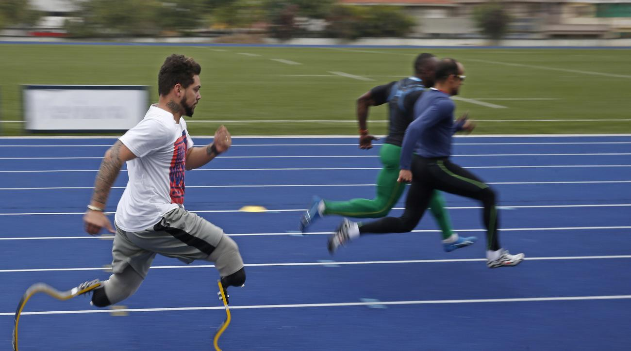In this July 22, 2016 photo, athlete Alan Fonteles, from Brazil, left, who competes mainly in category T44, trains ahead the Paralympic Games athletics events in Sao Paulo, Brazil. Only a last-minute Brazilian government bailout has helped save the Paraly