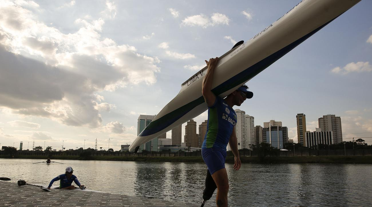In this July 1, 2016 photo, Brazil's Vander Lima carries his canoe as he trains for the Paralympic Games in Sao Paulo, Brazil. Only a last-minute Brazilian government bailout has helped save the Paralympic Games from a shortfall in the local, privately fu
