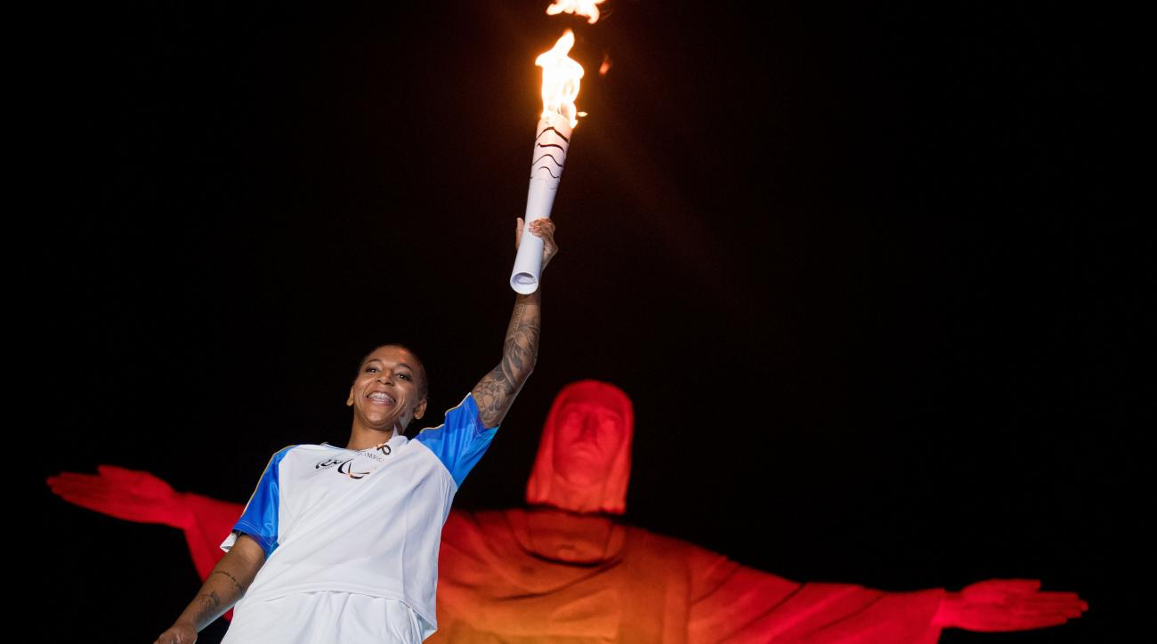 Brazilian judo gold medalist Rafaela Silva, carries the Paralympic torch in front of the Christ the Redeemer statue on its way for the opening ceremony in Rio de Janeiro, Brazil, Tuesday, Sept. 6, 2016.  (AP Photo/Mauro Pimentel)