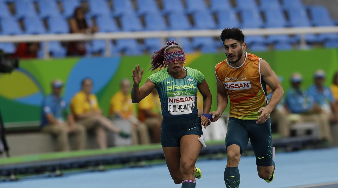 Brazil's Terezinha Guilhermina, accompanied by her guide Rafael Lazarini, competes in the women's 100-meter T11 semifinal 2 athletics event in Olympic Stadium, during the Paralympic Games, in Rio de Janeiro, Brazil, Friday, Sept. 9, 2016. (AP Photo/Leo Co