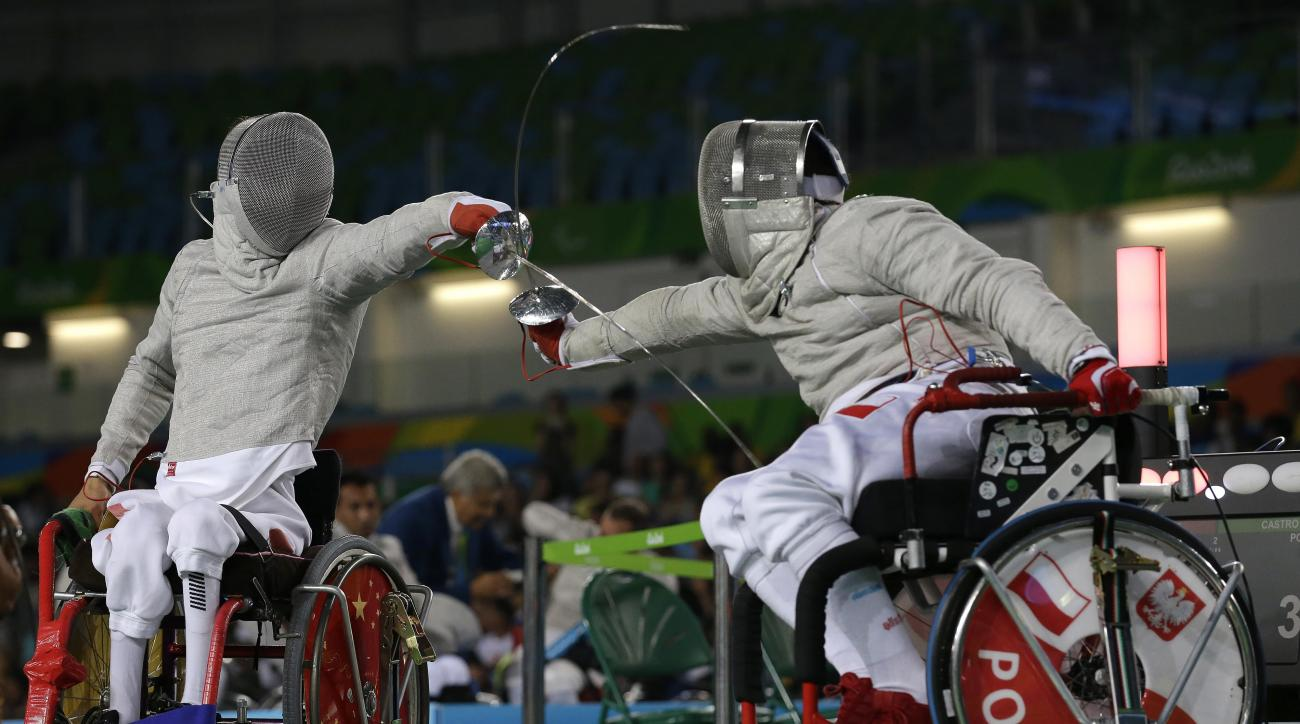 Yanke Feng, from China, left, competes with Adrian Castro, from Poland, in the men's individual sabre, category B, wheelchair fencing event at the Paralympic Games in Rio de Janeiro, Brazil, Monday, Sept. 12, 2016. (AP Photo/Leo Correa)