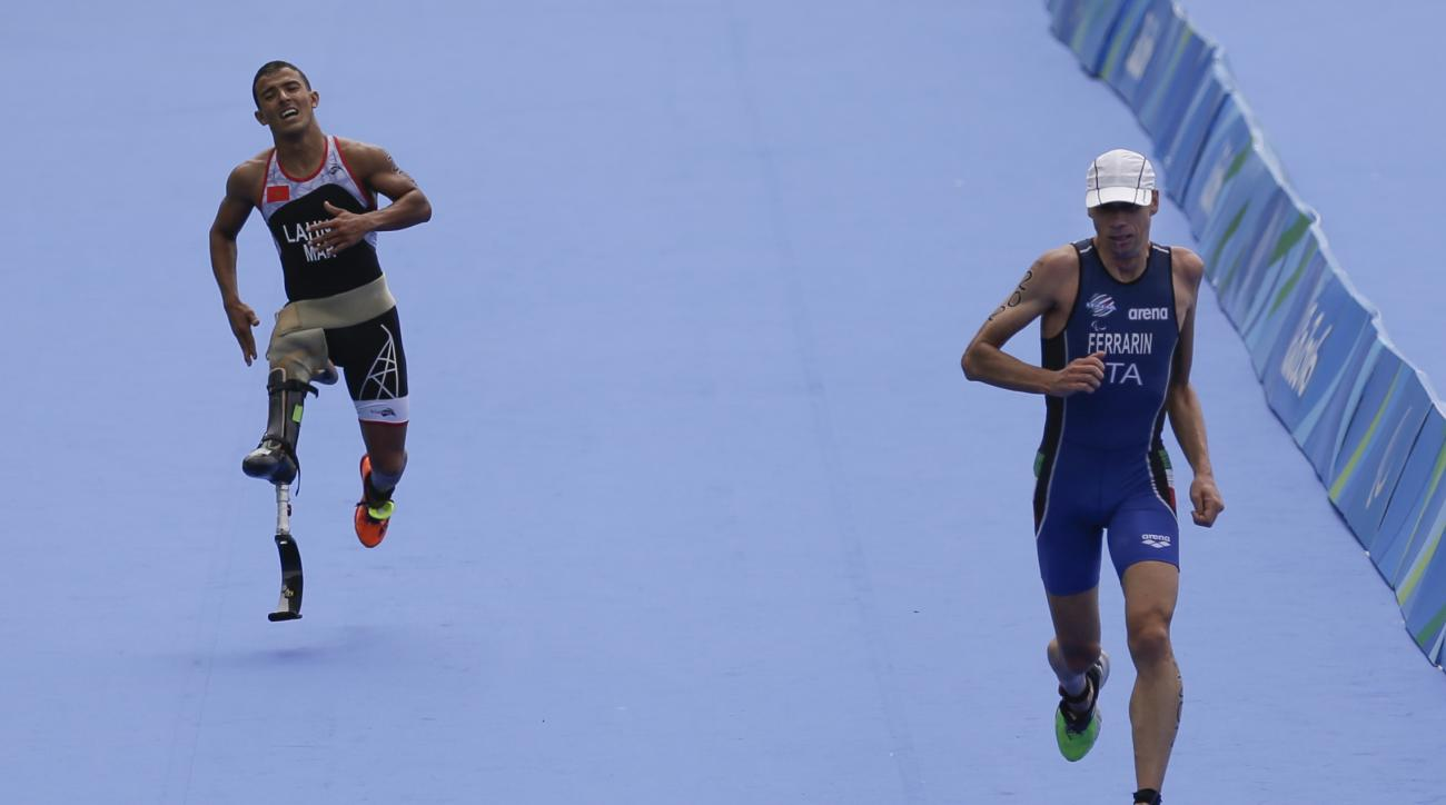 In this Sept. 10, 2016 photo, Italy's Michele Ferrarin, right, finishes in second place, followed by Morocco's Mohamed Lahna, in the men's triathlon PT2 athletics event at the Paralympic Games, on Copacabana beach, in Rio de Janeiro, Brazil. The Paralympi