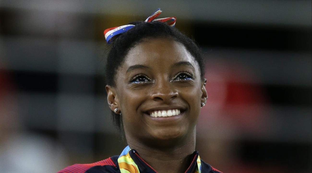 FILE - In this Aug. 16, 2016, file photo, United States' Simone Biles stands during the national anthem after winning the gold medal in the women's floor exercise at the 2016 Summer Olympics in Rio de Janeiro, Brazil. Confidential medical data of gold med
