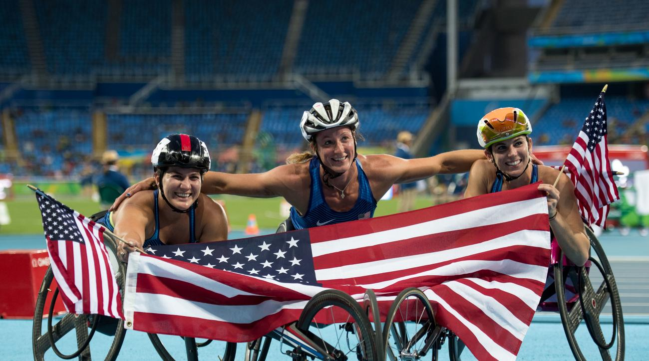 In this photo released by the IOC, silver medallist Chelsea McClammer, from left, gold medallist Tatyana McFadden, and bronze medallist Amanda McGrory, all of the United States, pose for a photo with their countrys national flag, after sweeping the podium