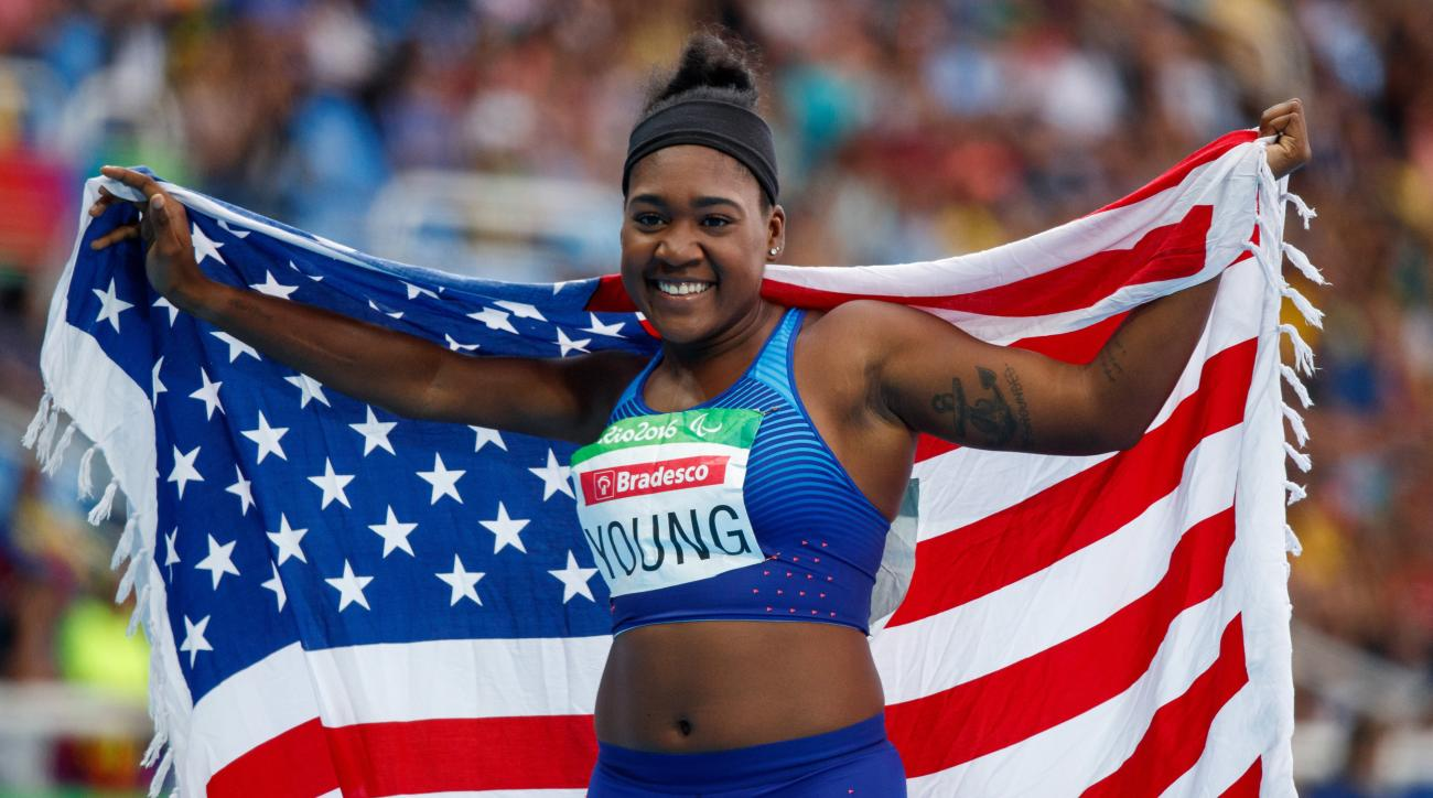 In this photo released by the IOC, Deja Young, of the United States, poses for a photo with her countrys national flag after winning the gold medal in the women's 200-meter - T47 final athletics event, at the Olympic Stadium, during the Paralympic Games i