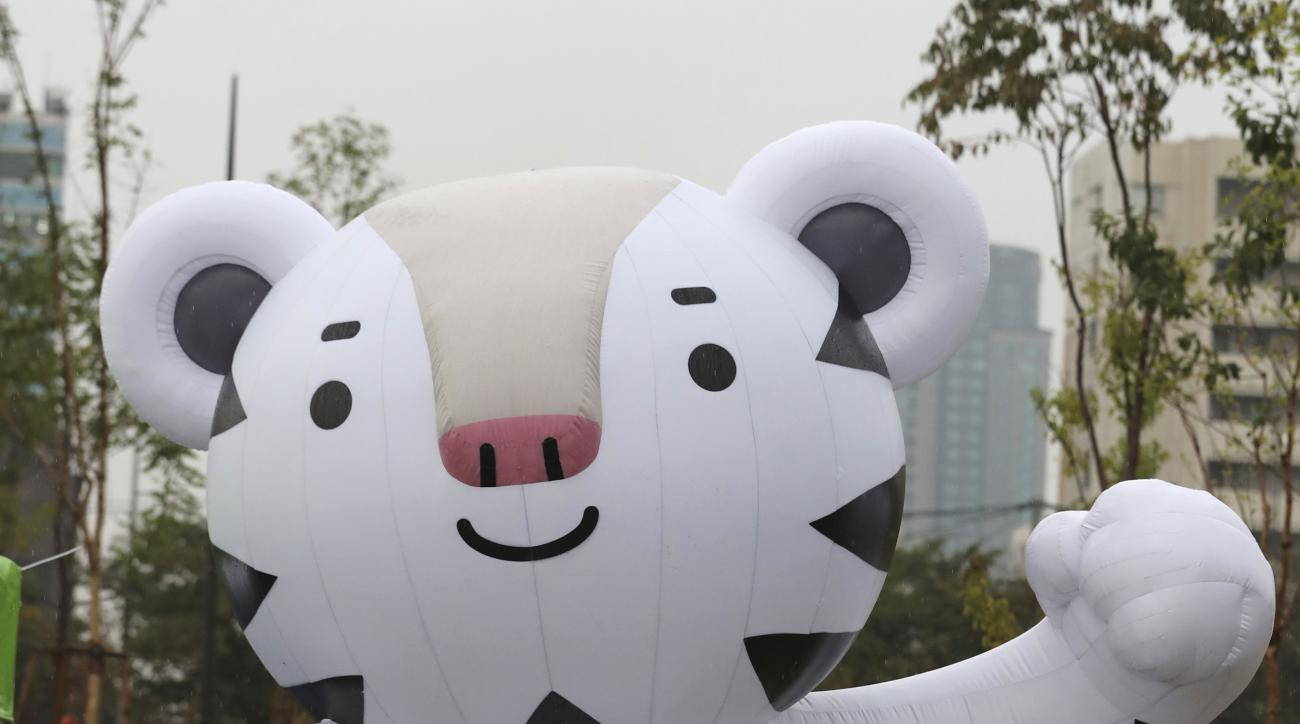 A woman walks by an official mascot of the 2018 PyeongChang Olympic Winter Games, white tiger Soohorang, before the event to mark the start of the 500-day countdown in Seoul, South Korea, Tuesday, Sept. 27, 2016. With 500 days until the Olympic cauldron i