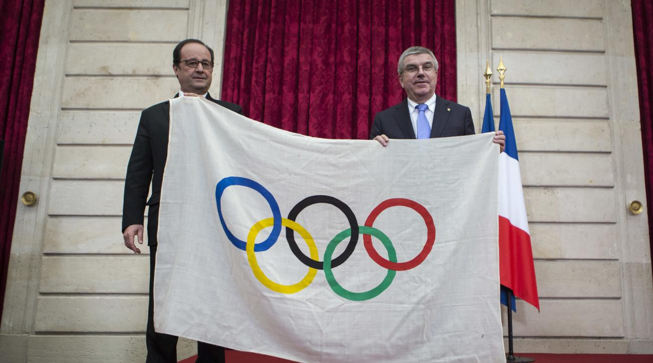 French President Francois Hollande, left, poses with International Olympic Committee President Thomas Bach, after Bach received an Olympic flag from the 1924 Olympics games during a meeting at the Elysee Palace in Paris, Sunday, Oct. 2, 2016. Paris, which