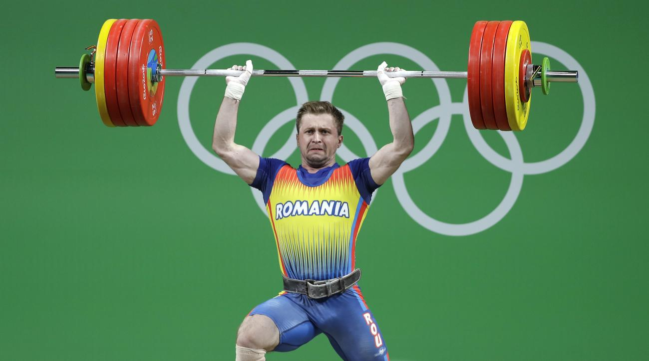FILE- In this Friday, Aug. 12, 2016 file photo, Gabriel Sincraian, of Romania, competes in the men's 85kg weightlifting competition at the 2016 Summer Olympics in Rio de Janeiro, Brazil. The International Weightlifting Federation says Sincraian, who won a