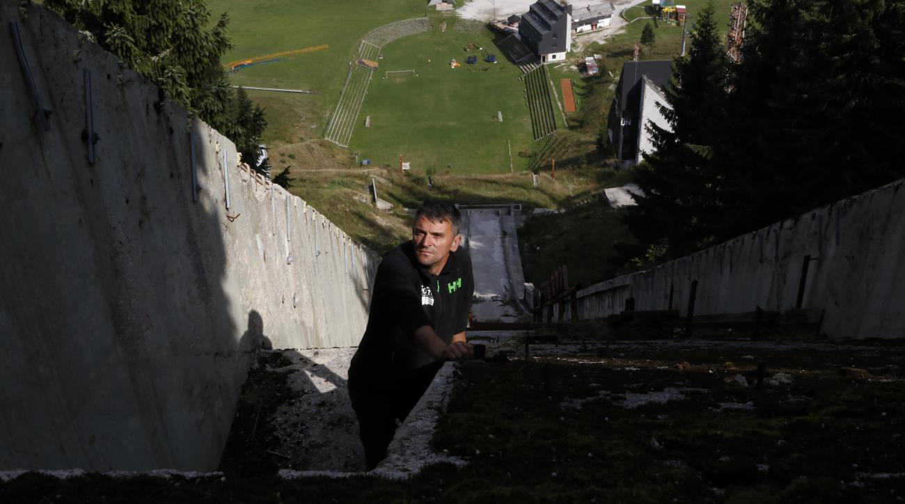 In this photo taken on Thursday, Sept. 15, 2016, Bosnian sports enthusiast Selver Merdanovic looks on from a destroyed ski jump facility at the mount Igman near Sarajevo.  Sports enthusiasts and former athletes in Bosnia have taken it upon themselves to r