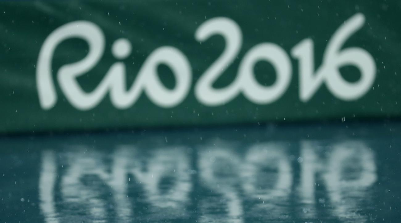 FILE - In this  Aug. 15, 2016 file photo, the Olympic logo is reflected on the wet floor as the athletics competitions of the Summer Olympics are suspended due to the pouring rain in Rio de Janeiro, Brazil. Workers employed at the Rio Olympics are ready t