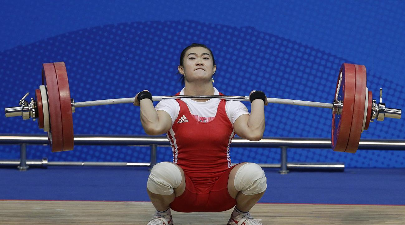 FILE - In this Tuesday, Nov. 16, 2010, file photo, Kazakhstan's Maiya Maneza attempts a lift during the women's 63kg weightlifting at the 16th Asian Games in Guangzhou, China. Kazakhstan says there are retrospective disqualifications from the 2008 games f
