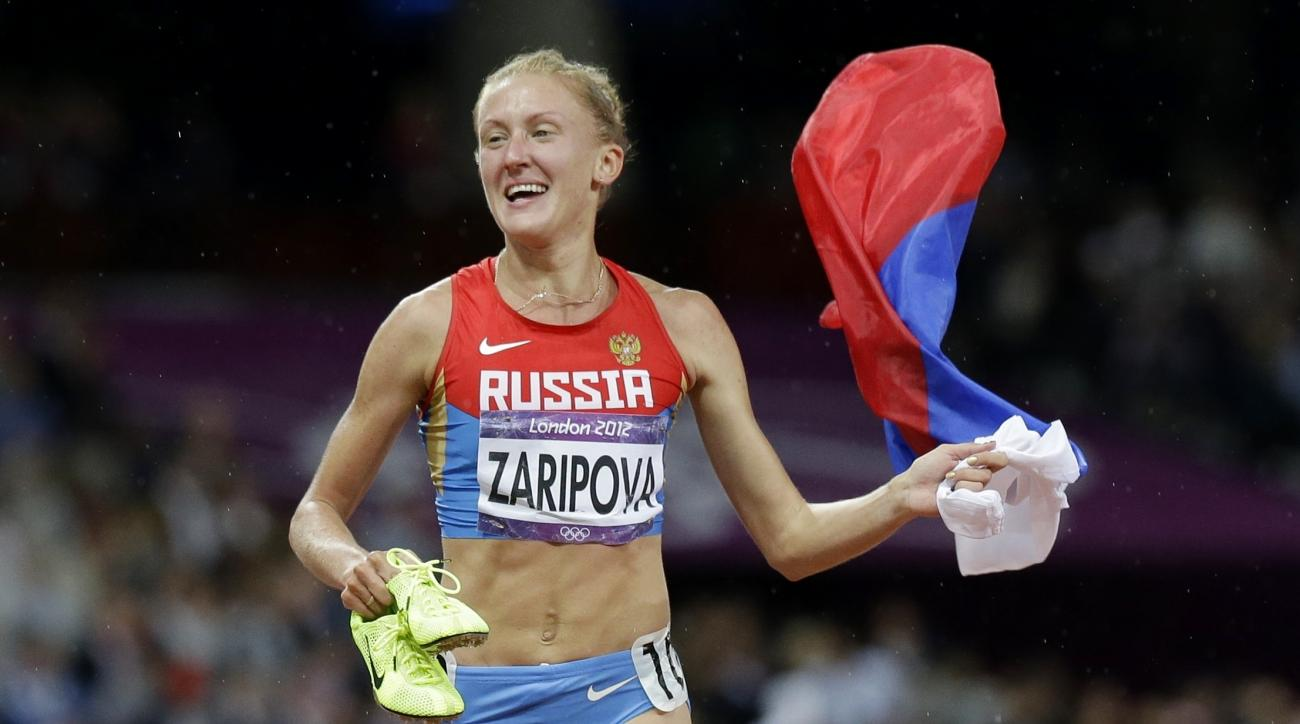 FILE - In this Monday, Aug. 6, 2012 file photo, Russia's Yulia Zaripova carries her national flag as she celebrates her win in the women's 3000-meters steeplechase during the athletics in the Olympic Stadium at the 2012 Summer Olympics, London. Zaripova,