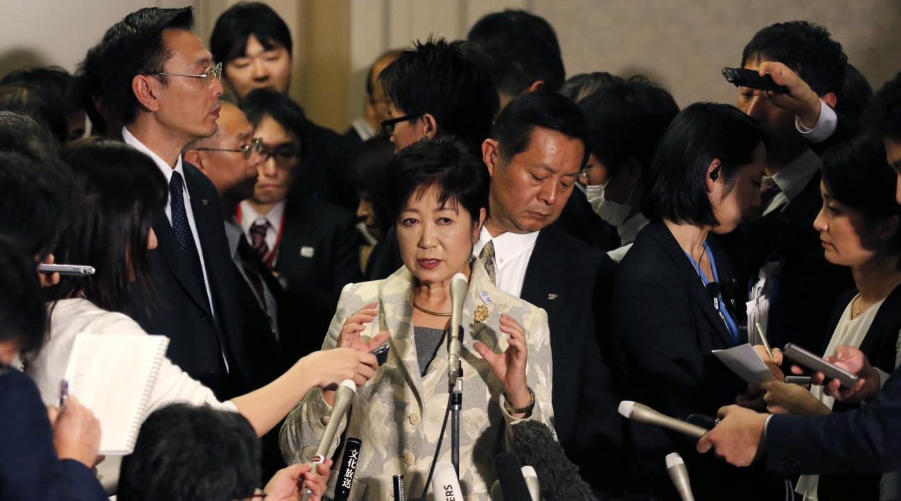 Tokyo Gov. Yuriko Koike, center, is surrounded by the media after IOC debriefing in Tokyo Tuesday, Nov. 29, 2016. Top international and Japanese Olympic officials discussing three expensive venues and cost cutting measures have agreed to keep two - rowing