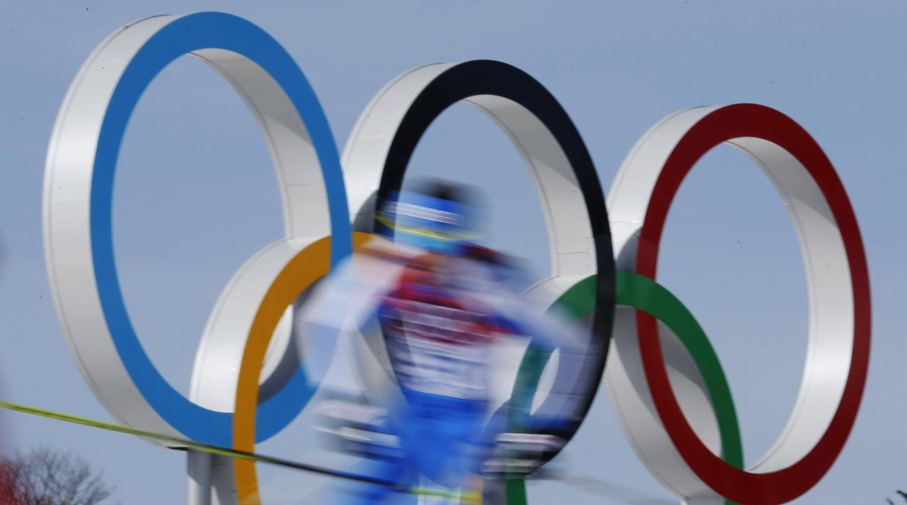 FILE - In this Feb. 23, 2014 file photo taken with slow shutter speed, athletes pass by the Olympic rings during the men's 50K cross-country race at the 2014 Winter Olympics in Krasnaya Polyana, Russia. (AP Photo/Dmitry Lovetsky, File)