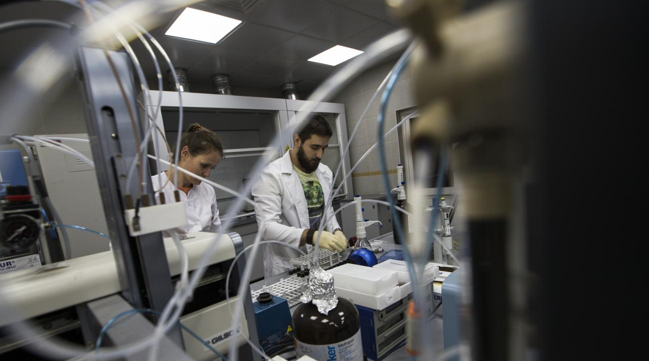 FILE- In this Tuesday, May 24, 2016, file photo employees Natalya Bochkaryova, left, and Ilya Podolsky work at the Russia's national drug-testing laboratory in Moscow, Russia.  It was at this laboratory, and its former site elsewhere in Moscow, that lab d