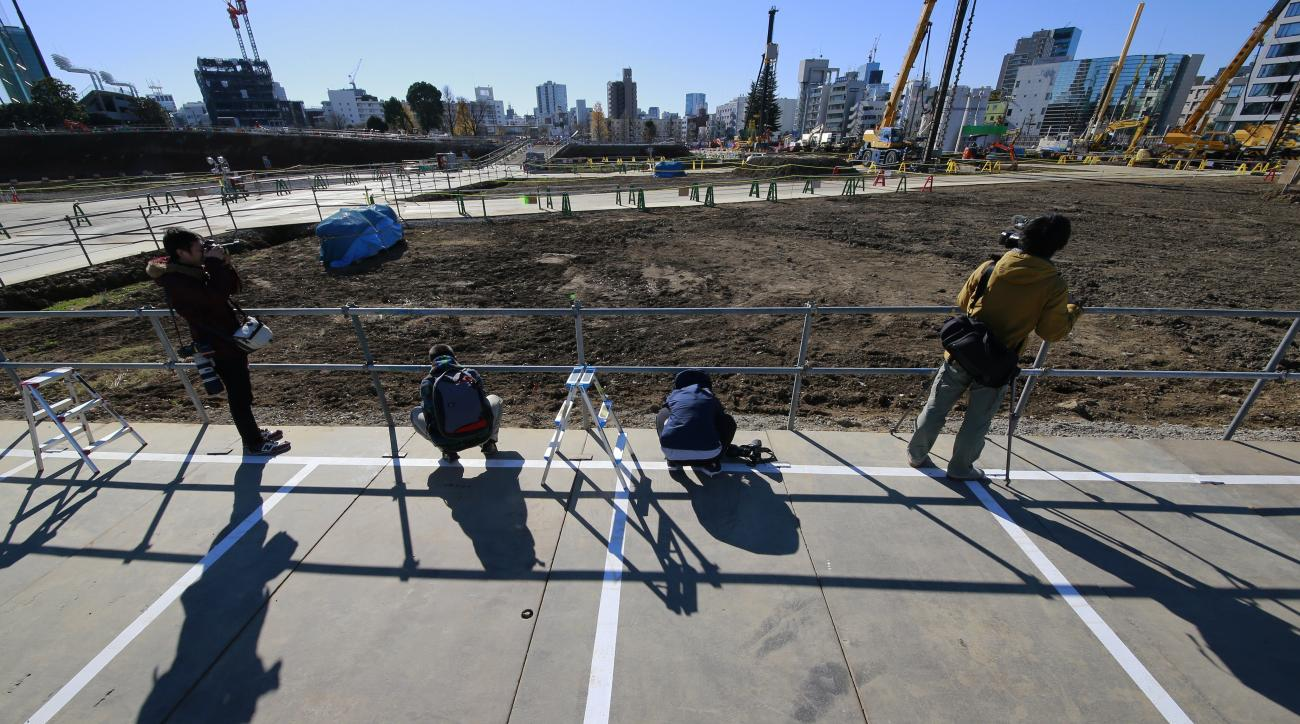 FILE - In this Dec. 11, 2016 file photo, photographers take a photo of the site of new national stadium after a groundbreaking ceremony in Tokyo. Japanese media say Tokyo Olympic organizers will present their first official cost estimate for the 2020 Game