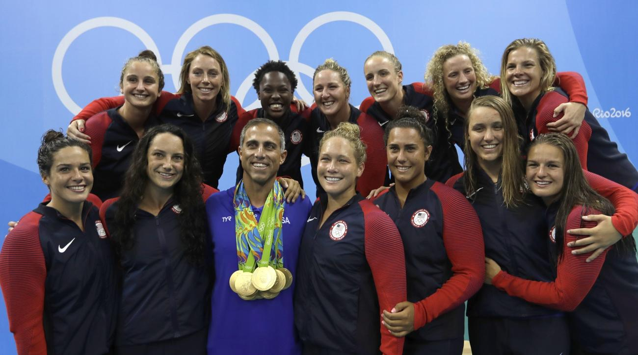FILE - In this Aug. 19, 2016, file photo, members of United States women water polo team pose with a coach Adam Krikorian during the medals ceremony at the 2016 Summer Olympics in Rio de Janeiro, Brazil. U.S. water polo coaches Adam Krikorian and Dejan Ud