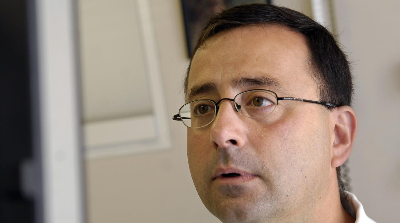 FILE - In this July 15, 2008, file photo, Dr. Larry Nassar works on the computer after seeing a patient in Michigan. A woman says Michigan States womens gymnastics coach downplayed her concerns about treatments by a sports doctor in the late 1990s and war