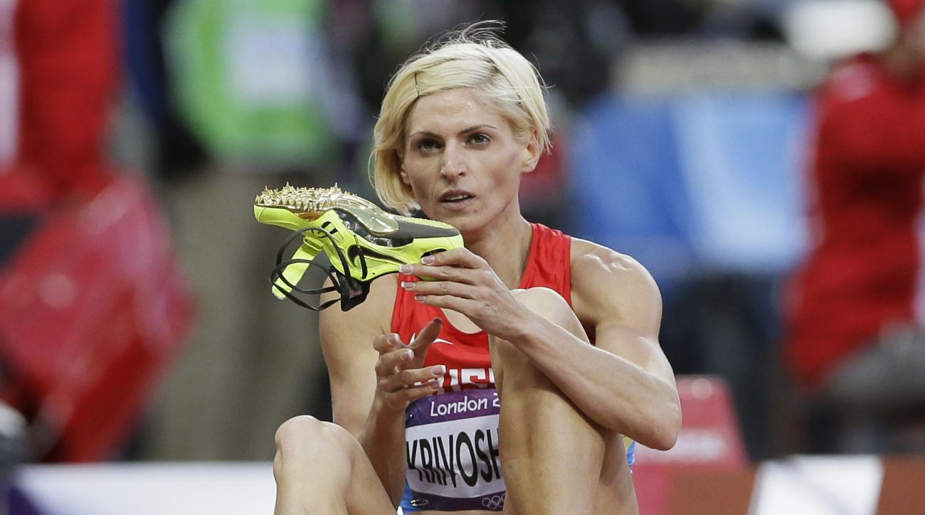 FILE - In this Aug. 4, 2012 file photo Russia's Antonina Krivoshapka takes off her shoes following a women's 400-meter semifinal during the athletics in the Olympic Stadium at the 2012 Summer Olympics, London. The IOC said Wednesday, Feb. 1, 2017 it has s