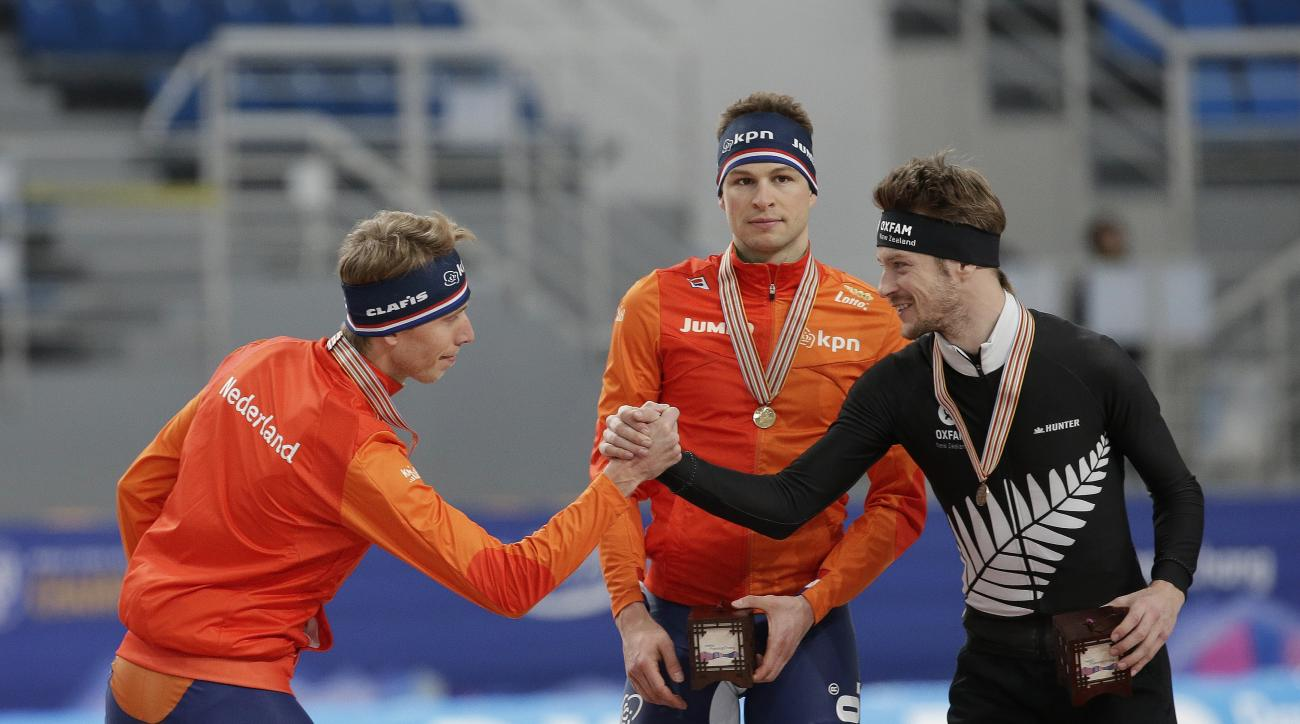The second Jorrit Bergsma, left, of the Netherlands shakes hands with third placed Peter Michael of New Zealand as winner Sven Kramer, center, of the Netherlands stands during an award ceremony of the men's 5,000-meter race of the ISU world single distanc