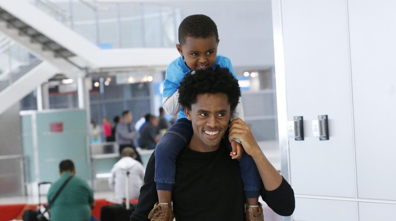 Olympic silver medalist Feyisa Lilesa, of Ethiopia, carries his son Sora, 3, and pulls along his daughter Soko, 5, after picking up his family at Miami International Airport, Tuesday, Feb. 14, 2017, in Miami. Lilesa arrived in the U.S. on a special skills