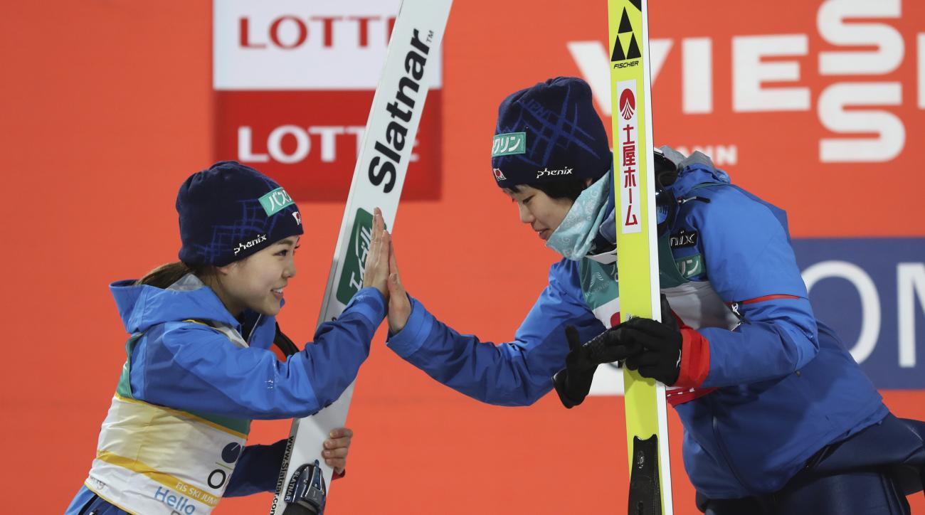 Second placed Japan's Sara Takanashi, left, gets a high-five with winner Japan's Yuki Ito, right, during the award ceremony for the Normal Hill Individual of the FIS Ski Jumping World Cup in Pyeongchang, South Korea, Wednesday, Feb. 15, 2017. (AP Photo/Le